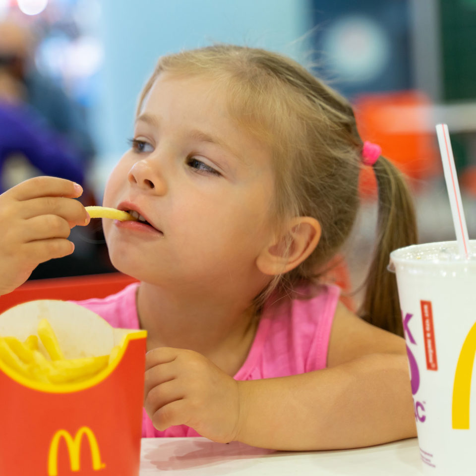 young-girl-eating-french-fries-at-mcdonalds